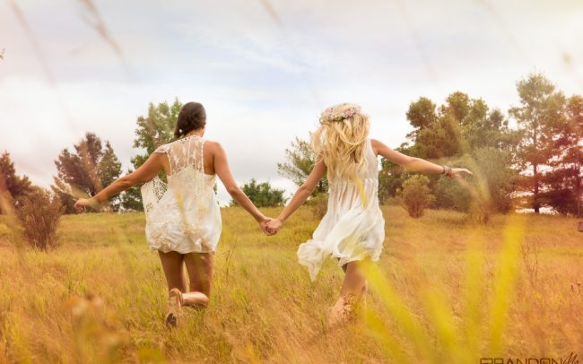 Portrait photography bohemian fashion female models with make-up and styling sunny day playful running through a field