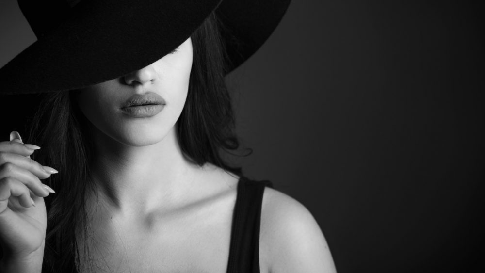Black & White Photo with Model Heileen Arias and Brandon Marsh Photography Dramatic Moody lighting focused on lips & holding hat fashion portrait
