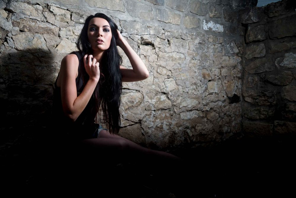 Grunge Model Portrait in rain in front of stone wall By Brandon Marsh Photography in downtown guelph, ontario