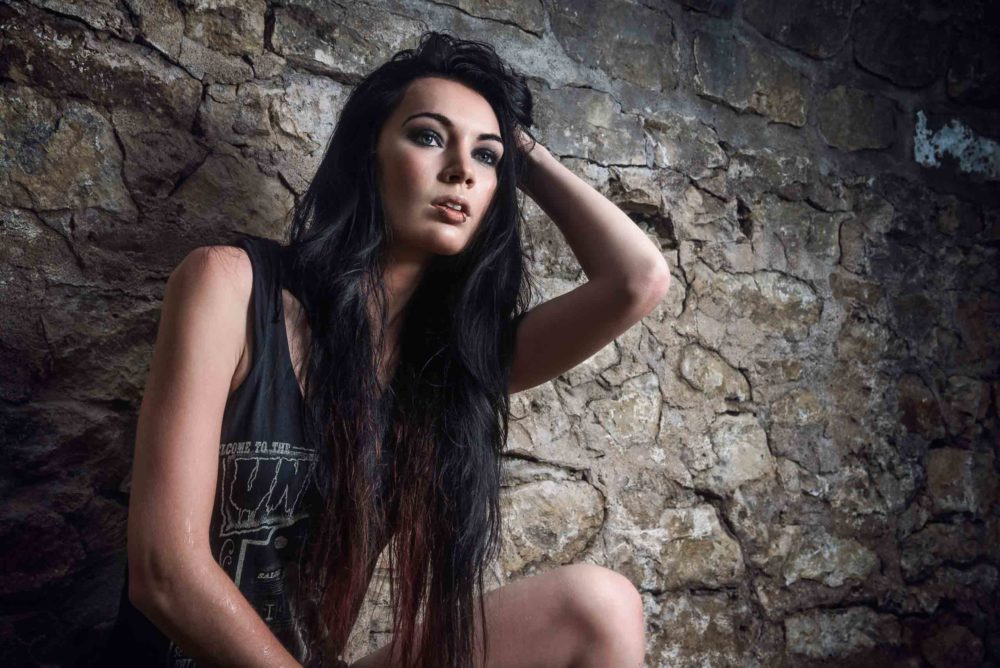 Grunge Female Model Portrait on location in front of stone wall touching hair in the rain By Brandon Marsh Photography in Downtown Guelph