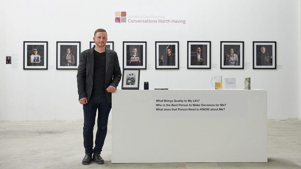 Photo of Brandon Marsh Photography standing in front of artwork for
