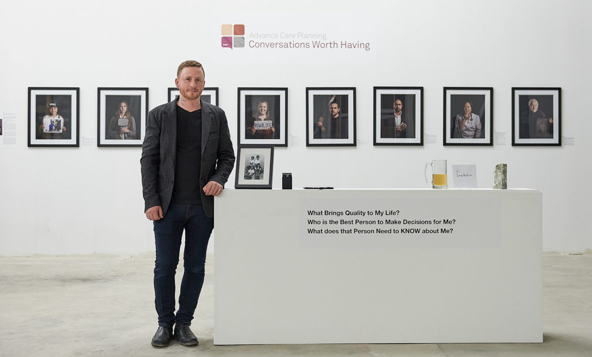 "Photo of Brandon Marsh Photography standing in front of artwork for ""KNOW"" art gallery event. Photo series to generate discussion about advance care planning and end of life care Photographed by Laurie Cadman Creative"