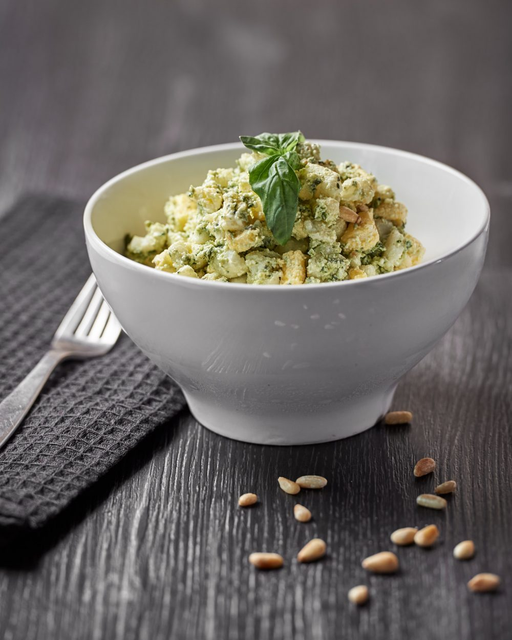 Food Photography of healthy scrambled egg breakfast with basil provided by egg solutions on a dark wood surface with scattered pine nuts Photographed by Brandon Marsh Photography