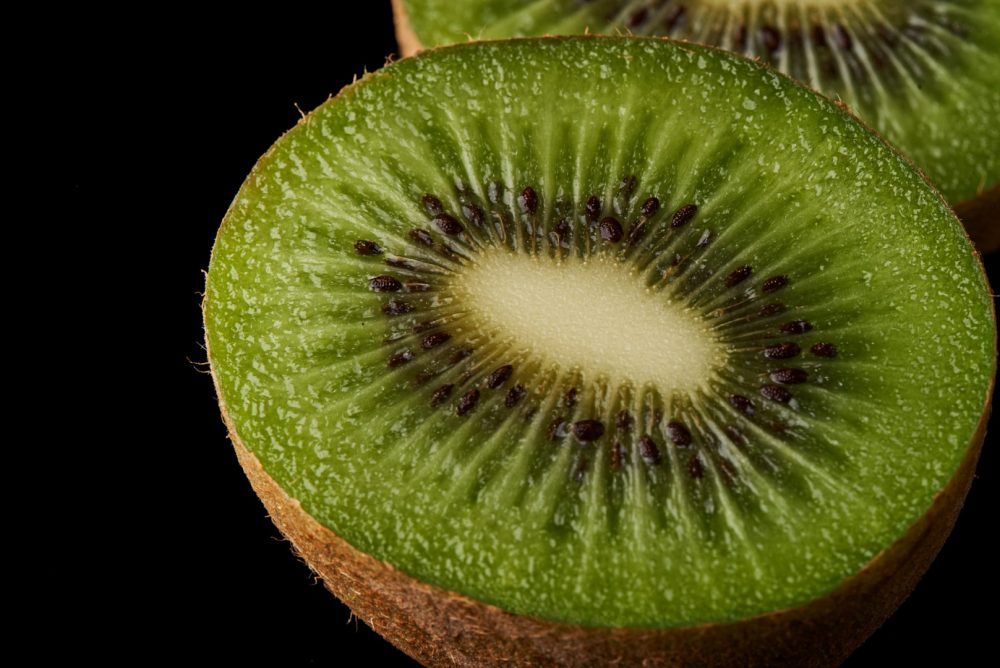 Moody Macro Food Photography of a Kiwi on a black backdrop Photographed by Brandon Marsh Photography