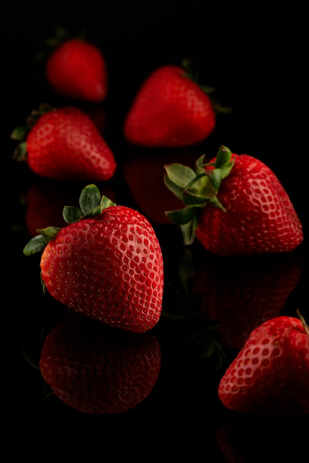 Food Photography of moody locally grown organic strawberries on a black reflective surface Photographed by Brandon Marsh Photography