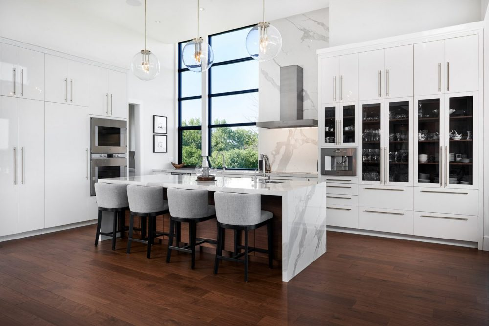 Architecture interior photography of an all white kitchen, massive window viewing a beautiful summer day, designed by Barzotti Woodworking LTD. Photographed by Brandon Marsh Photography