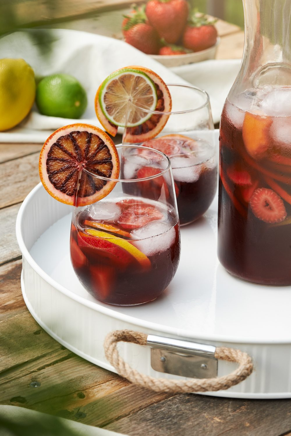 Food & Drink Photography of a pitcher of red wine sangria on a hot summer day. Serving tray placed on a picnic table with ingredients throughout the image  Photographed by Brandon Marsh Photography