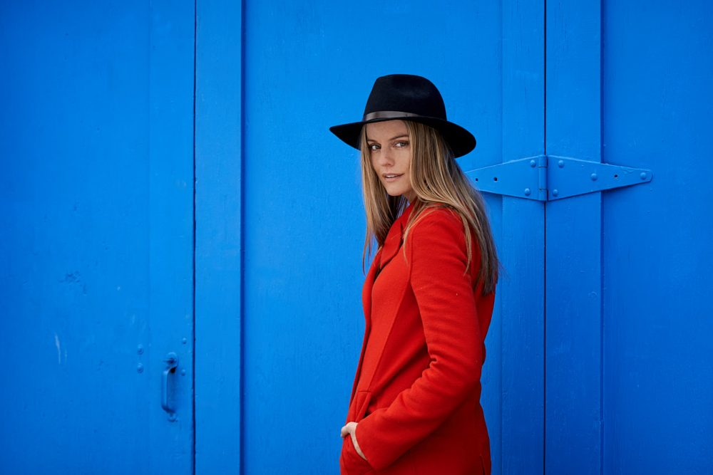 Lifestyle portrait of International Model Jennifer Steel in front of Blue doors wearing a hat and red winter jacket Photographed by Brandon Marsh Photography