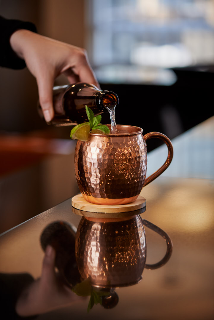 Lifestyle product photo of hand model pouring ginger beer into chefs gizmos moscow mule copper mugs on bar counter with background window light Photographed by Brandon Marsh Photography