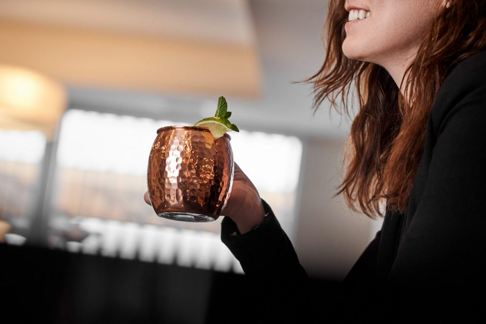 Lifestyle product photo of model smiling and holding a moscow mule in chefs gizmos copper mug, sitting at the bar in a lounge atmosphere Photographed by Brandon Marsh Photography