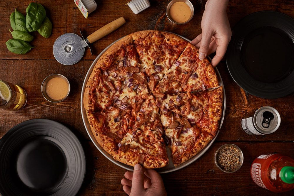 Overhead lifestyle food photography of pizza, condiments and ingredients on dark wood surface with hands reaching for the pizza Photographed by Brandon Marsh Photography