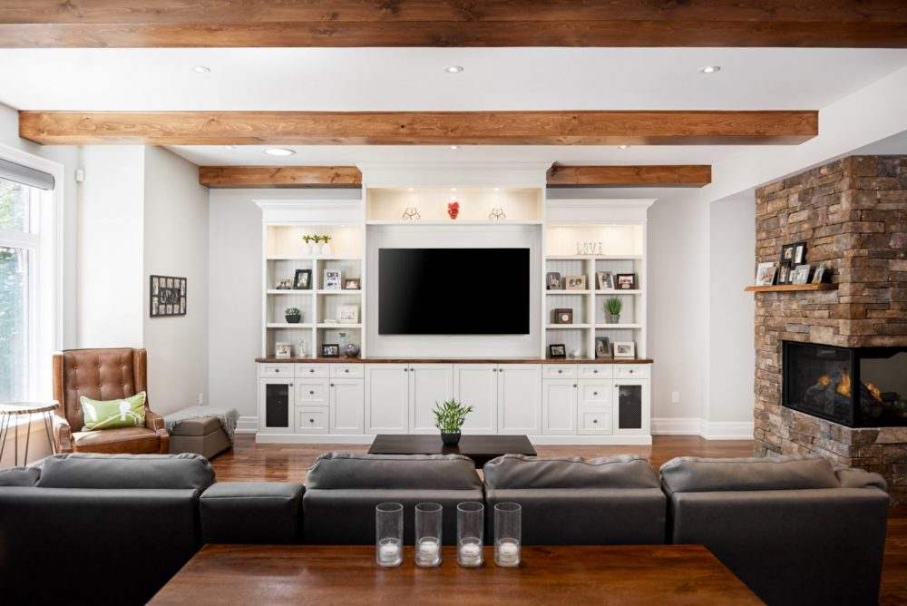 Architecture interior photography of a great room, wood beams, stone fireplace, cozy and a Wall TV unit designed by Barzotti Woodworking LTD. Photographed by Brandon Marsh Photography