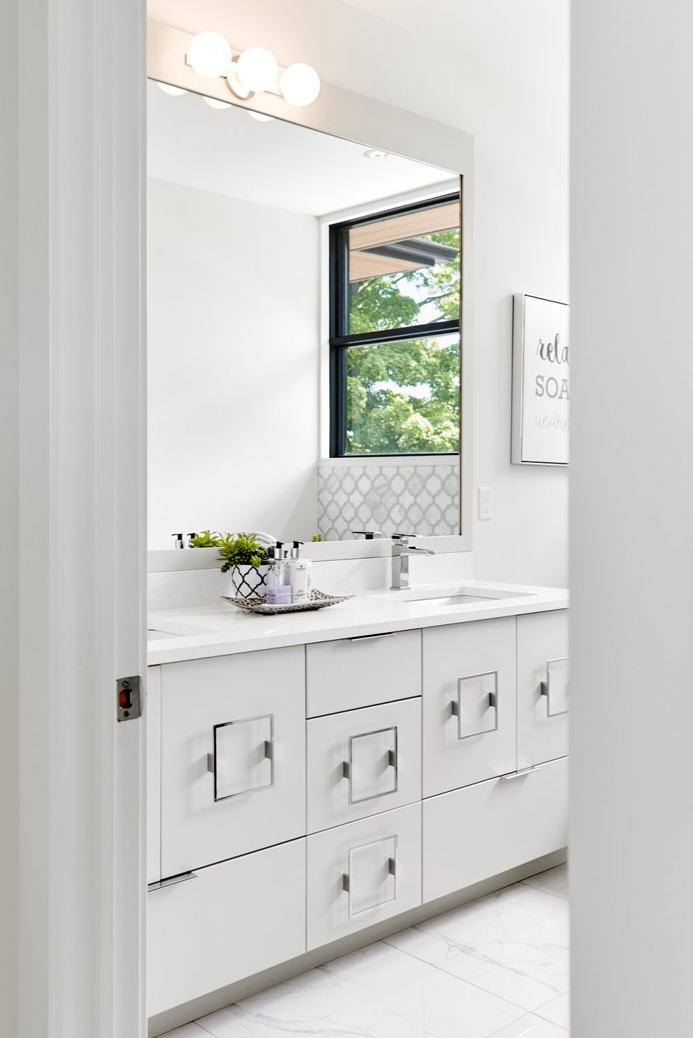 Architecture interior photography of a white bathroom with modern stainless steel drawer handles designed by Barzotti Woodworking LTD. Photographed by Brandon Marsh Photography