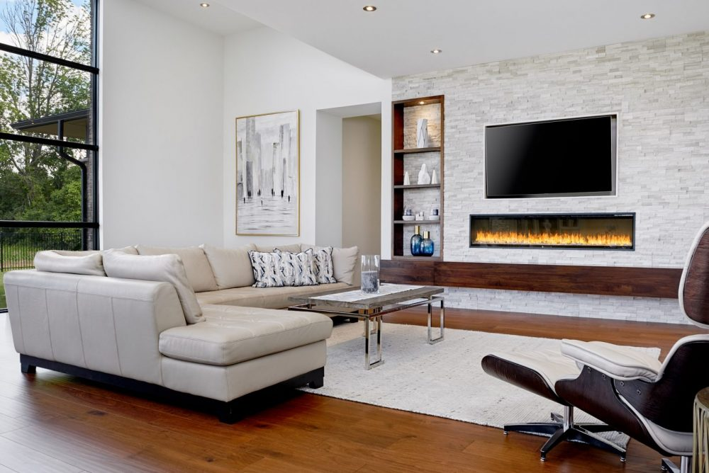 Architecture interior photography of a modern living room with massive floor to ceiling windows, wall fireplace and wood beam wall unit designed by Barzotti Woodworking LTD. Photographed by Brandon Marsh Photography