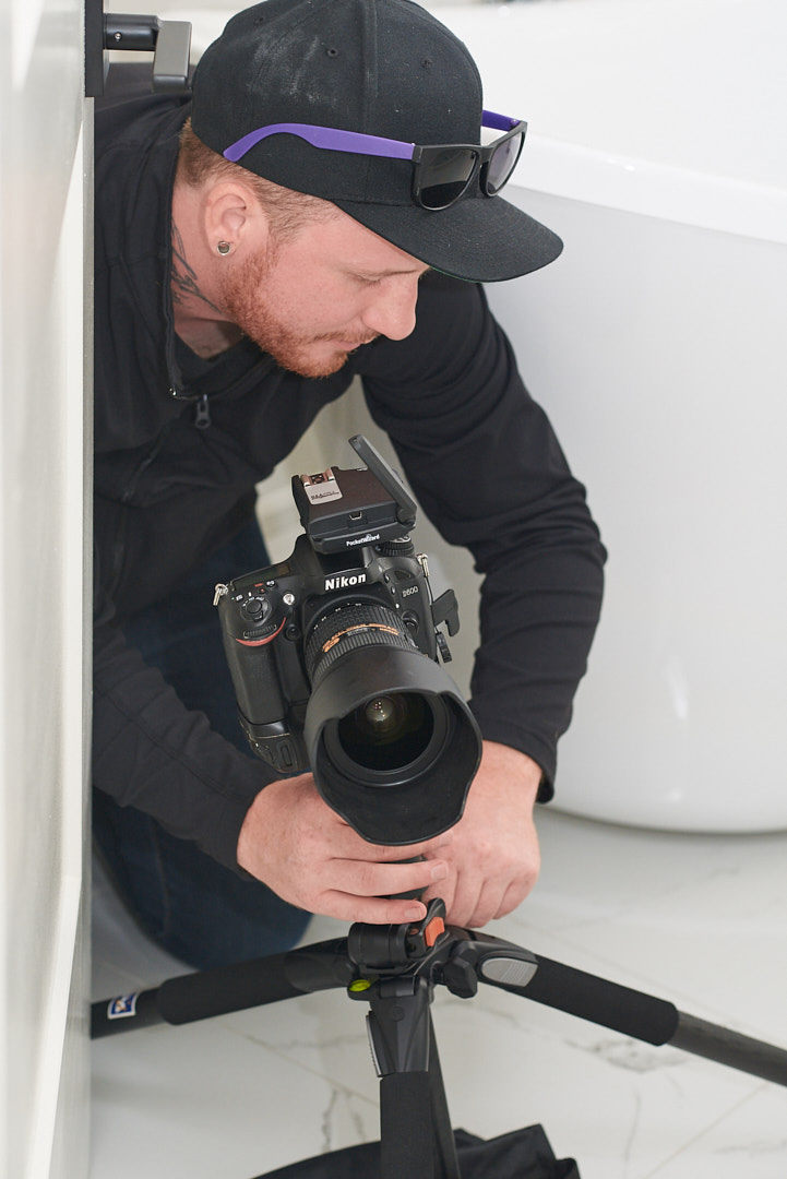 Behind the scenes photo of Brandon Marsh setting up tripod next to a toilet in a home in southern ontario to shoot interior images for Barzotti Woodworking  by Assistant Laurie Cadman Creative