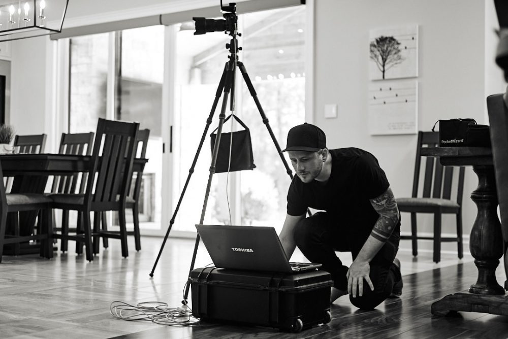 Behind the scenes photo of Brandon Marsh working on tethered laptop shooting interior images of a home in burlington, ontario in black and white by Assistant Laurie Cadman Creative